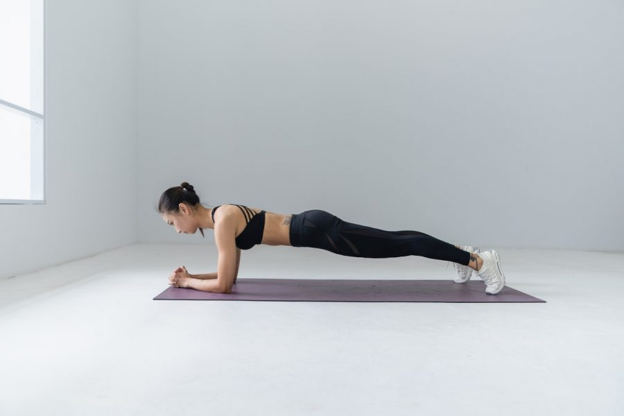 Girl doing plank. Plank is best easy home workout for belly