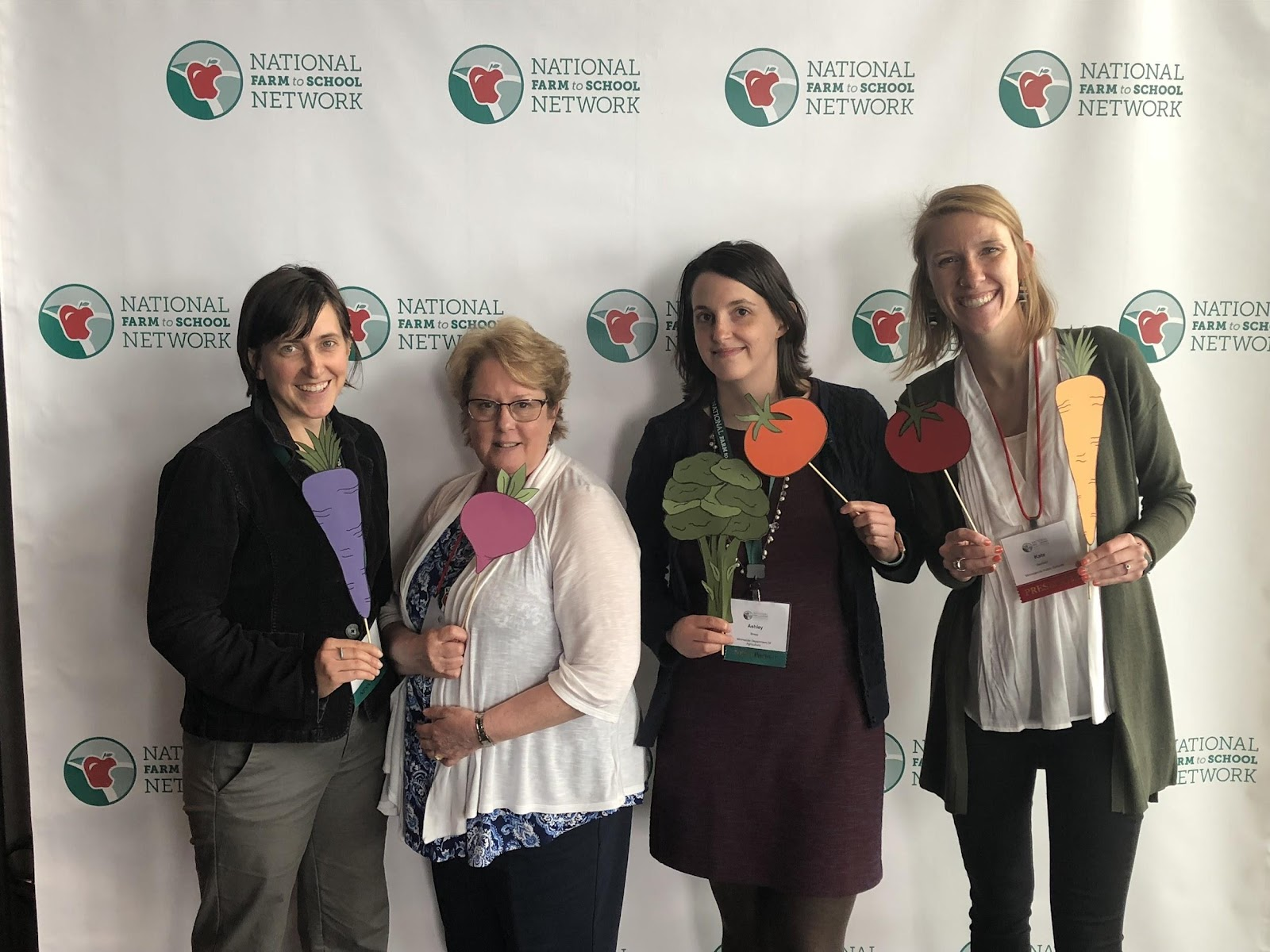 Workshop presenters from Minnesota, Grace Brogan, Carrie Frank, Ashley Bress and Kate Seybold (pictured L to R) pose for a photo with veggies at the 2018 National Farm to Cafeteria Conference.