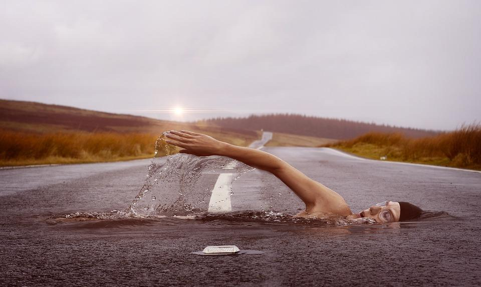 A swimmer swimming in a river which appears as a road