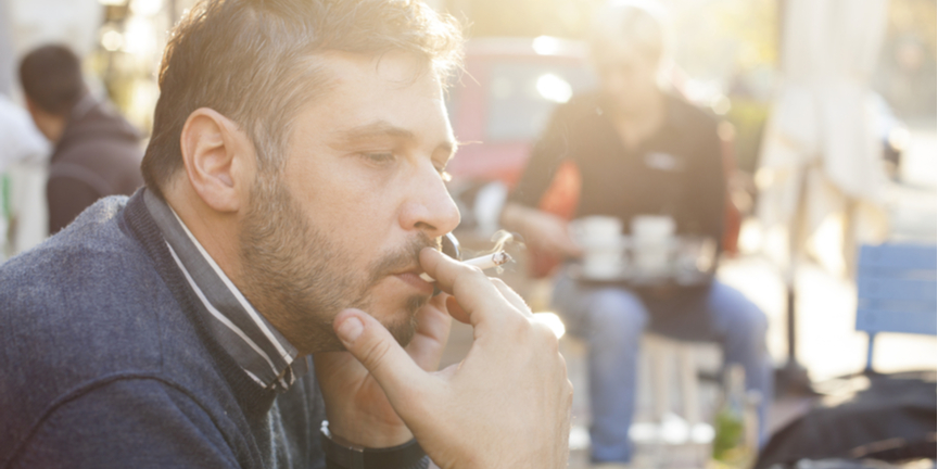 businessman-smoking-cigarette-while-on-phone