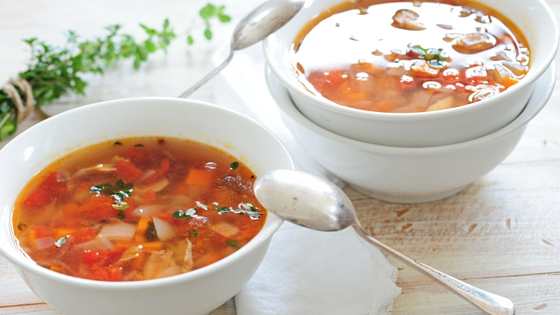 A couple of bowls of tomato based soup sitting on the table, garnished with herbs.