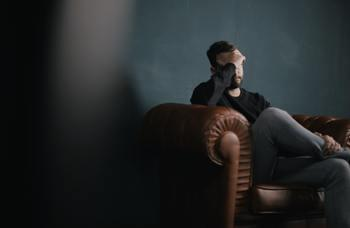 man sitting on the couch and feeling anxious