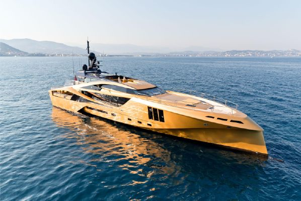 A super yacht sits like a golden blade floating in the water.