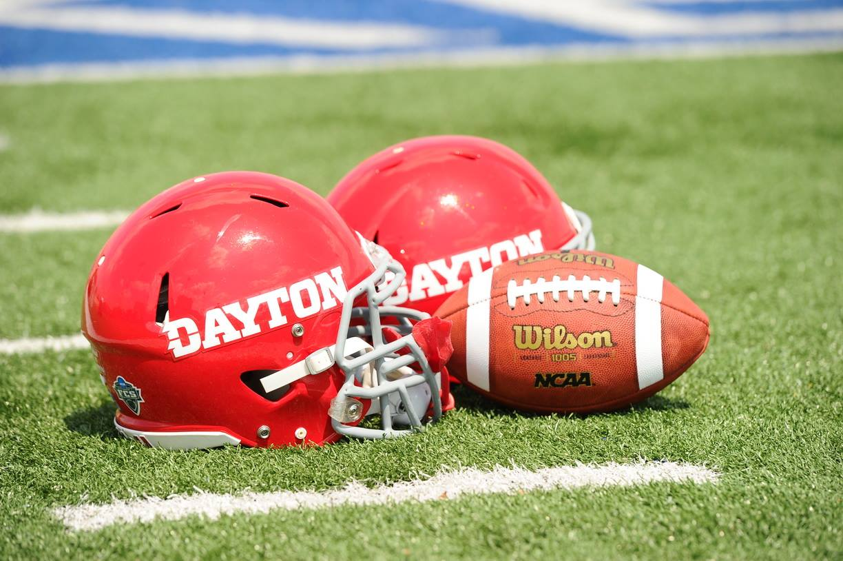 two Dayton Flyers football helmets next to a football on the field