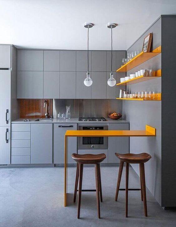 Cozinha com paredes, móveis e piso cinza, prateleiras e bancada amarelas e banco de madeira.