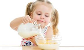 Girl pouring her milk