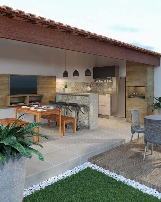 Area externa de casa com churrasqueira revestida de porcelanato imitando pedras, piso de cimento queimado, mesa de madeira com bancos, painel com TV, luminárias pendente e bancada de concreto com bancos.