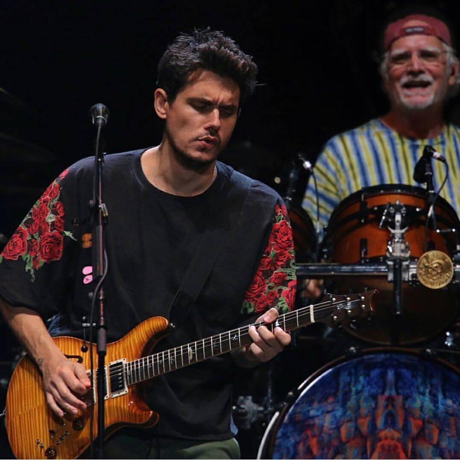 John Mayer playing the guitar at an event.