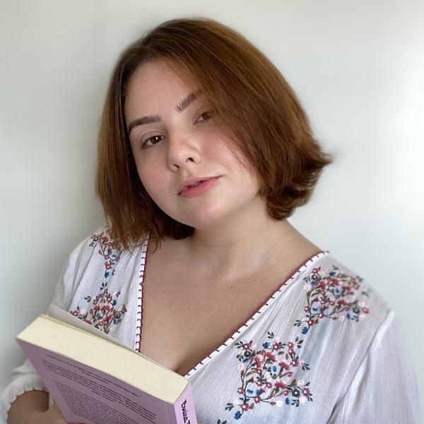 Mulher branca sorrindo para a câmera com os cabelos ruivos e soltos.