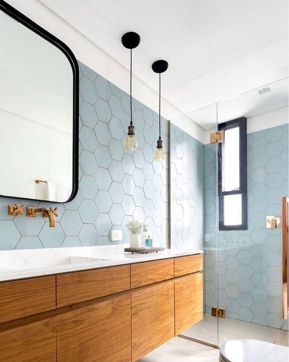 Banheiro com revestimento hexagonal azul claro  nas paredes, armário amadeirado com bancada da pia branca, torneira dourada, piso branco, lâmpadas pendentes,  box de vidro com detalhes dourados.