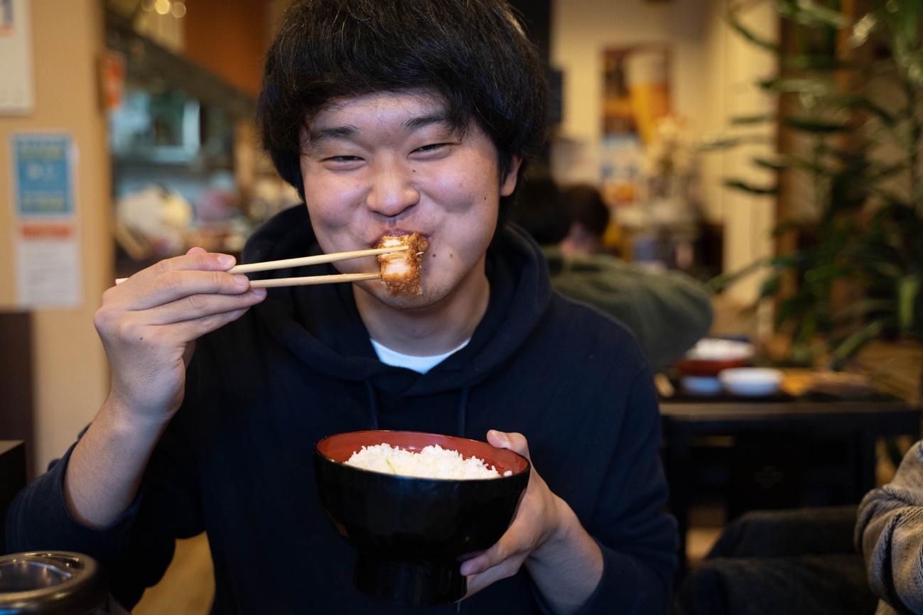 ピザを食べる男性  中程度の精度で自動的に生成された説明