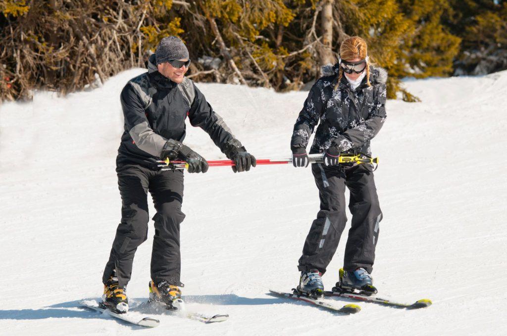 Profesor enseñando a esquiar a su alumna
