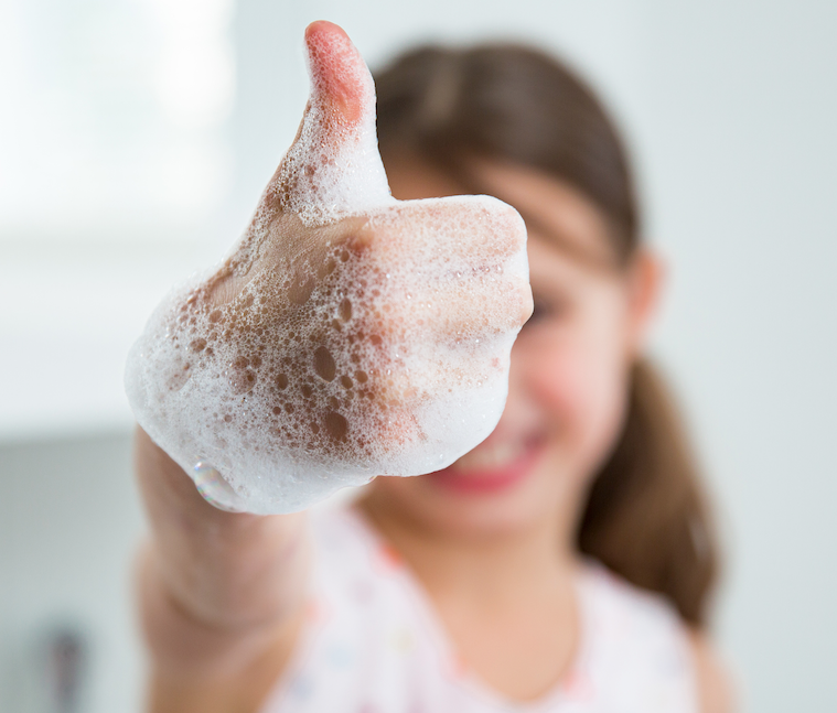 Schoolgirl with soapy hand giving thumbs-up after using a faucet upgraded with ARP, ESSER, and HEERF Funds