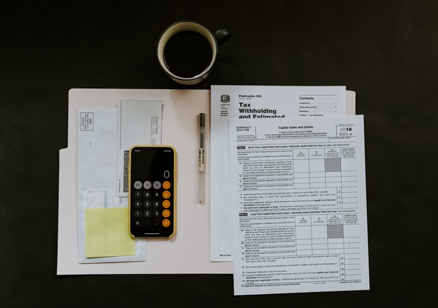 Tax documents and a calculator placed on a desk next to a cup of coffee