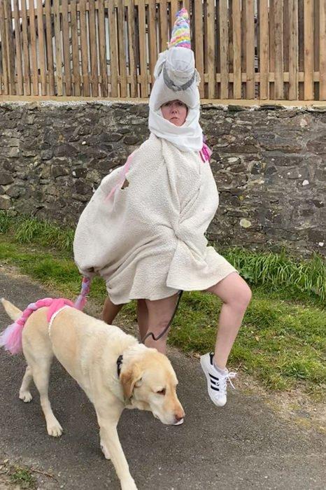 Mujer usa disfraz de unicornio mientras pasea a su perro