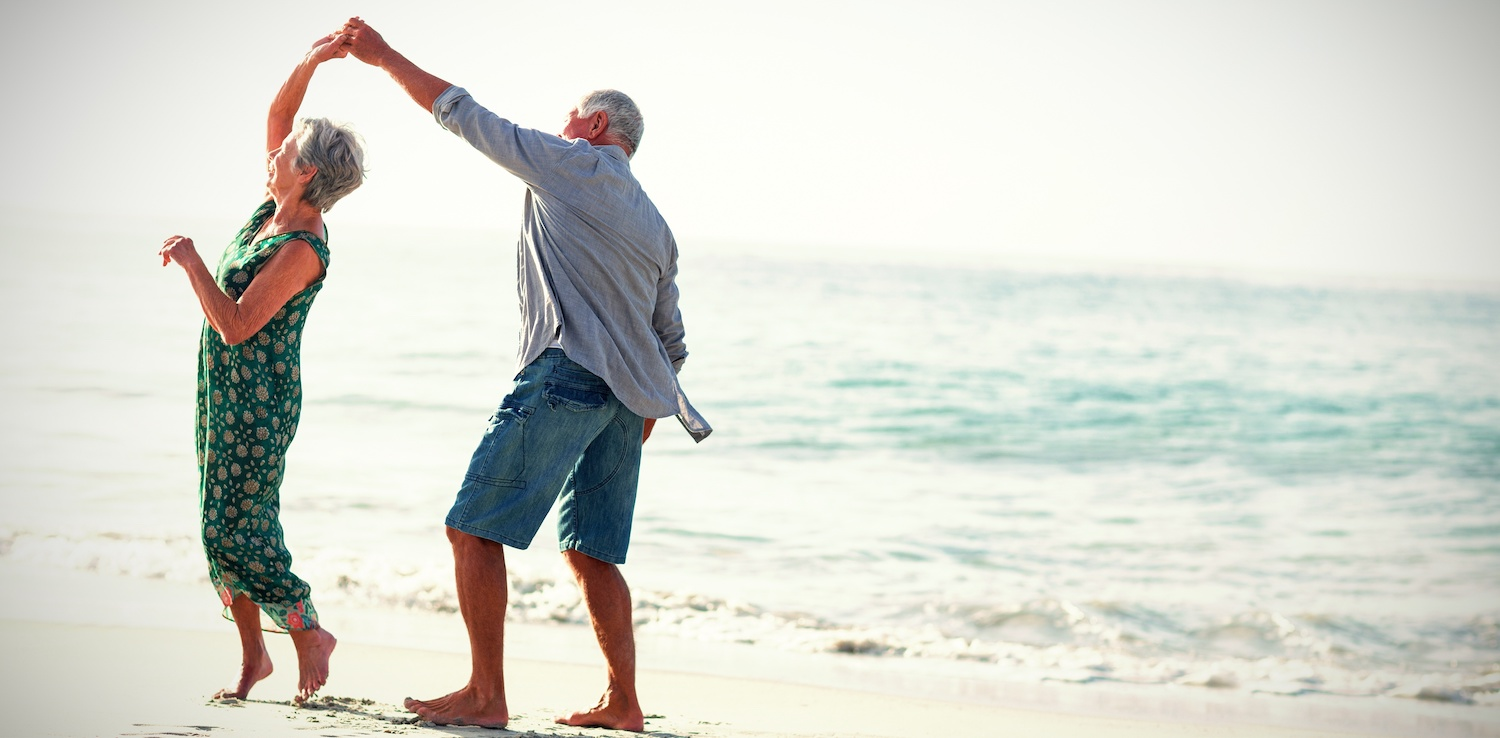 monthly dividend stocks: Elderly couple dancing at the beach