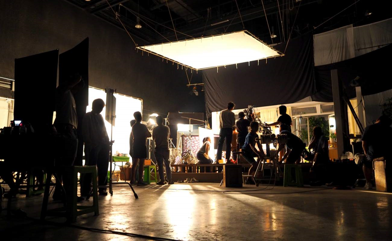 ALT: A behind-the-scenes shot from a set with the cast and crew hard at work.