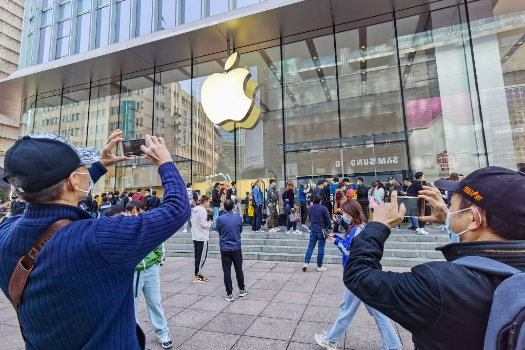 Customers queue to get their reserved iPhone 12 mobile phones at an Apple store in Shanghai on October 23, 2020. The Chinese Advertising Association, a CCP state-run entity, is working with Wechat's Tencent and Tiktok's ByteDance to circumvent Apple's upcoming privacy upgrade in iOS 14.5.