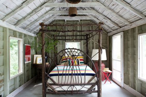 log canopy bed frame in an exposed-beam bedroom