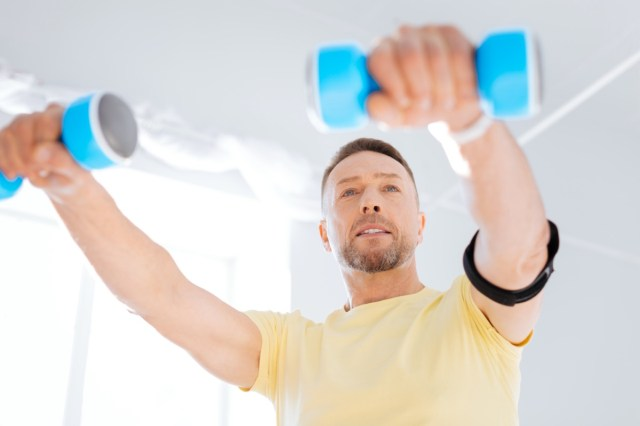 man smiling while using dumbbells and working out