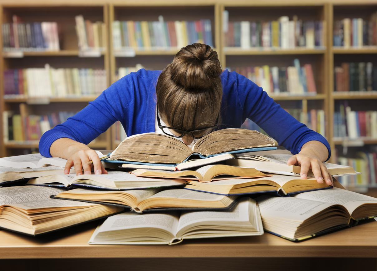 Woman looking overwhelmed with many open books