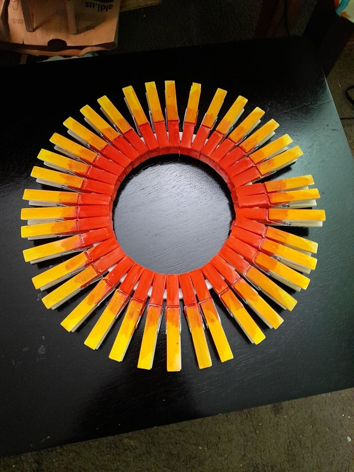 finished clothespin wreath meant to look like the sun