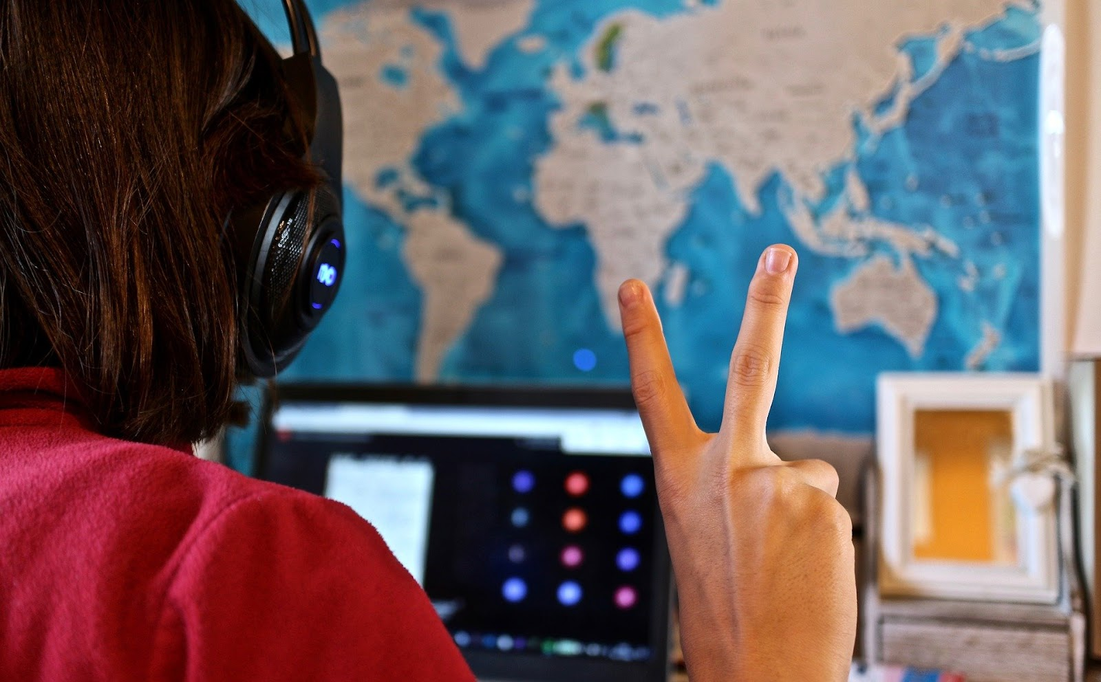 A person in front of a laptop, showing the peace sign