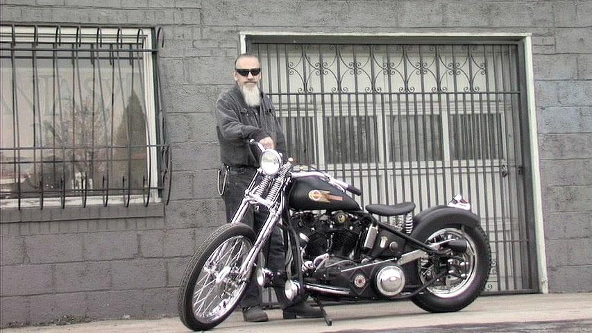 Biker and metal craftsman Dennis Goodson with his Harley bobber
