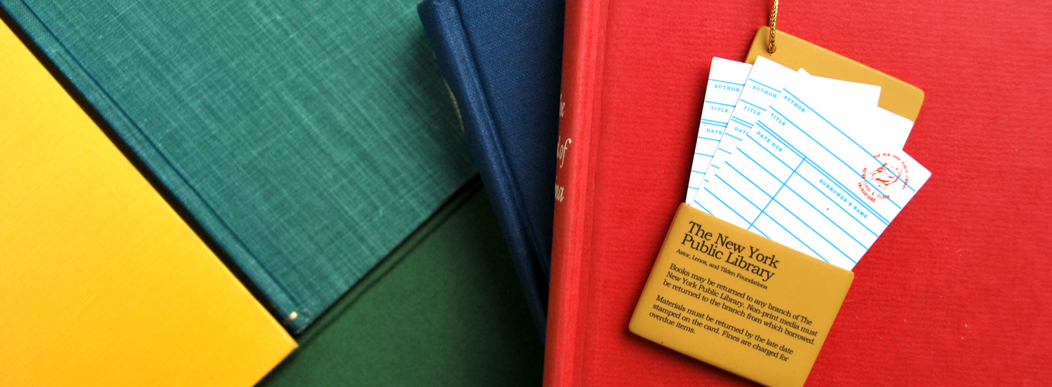 Colorful book covers with a New York Public Library check-out card on top of a red book