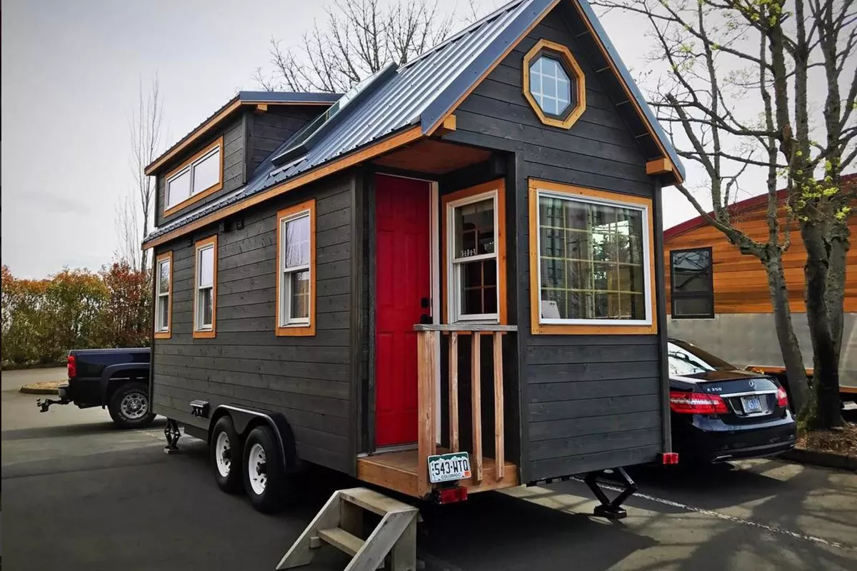 black tiny house on a trailer with wood accents, small front porch and pitched roof, tiny house kitchen ideas and photos