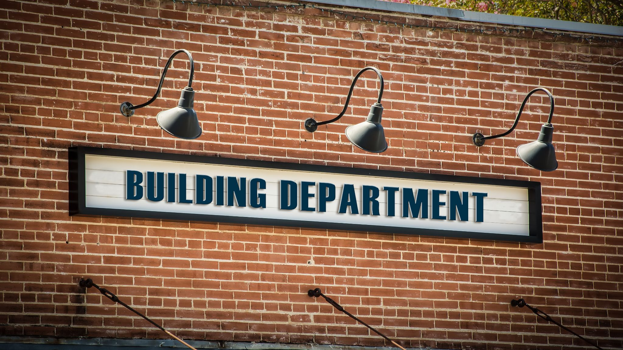 """""""Building department"""" sign on a brick wall of a structural engineer business."""