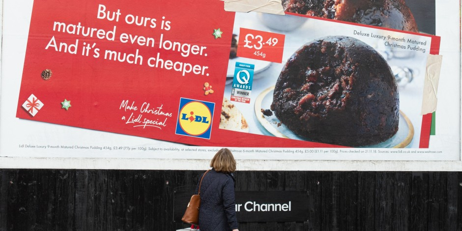 """A holiday billboard by Lidl showing their Christmas pudding and taking jabs at competitors with text """"But ours is matured even longer. And it's much cheaper."""""""