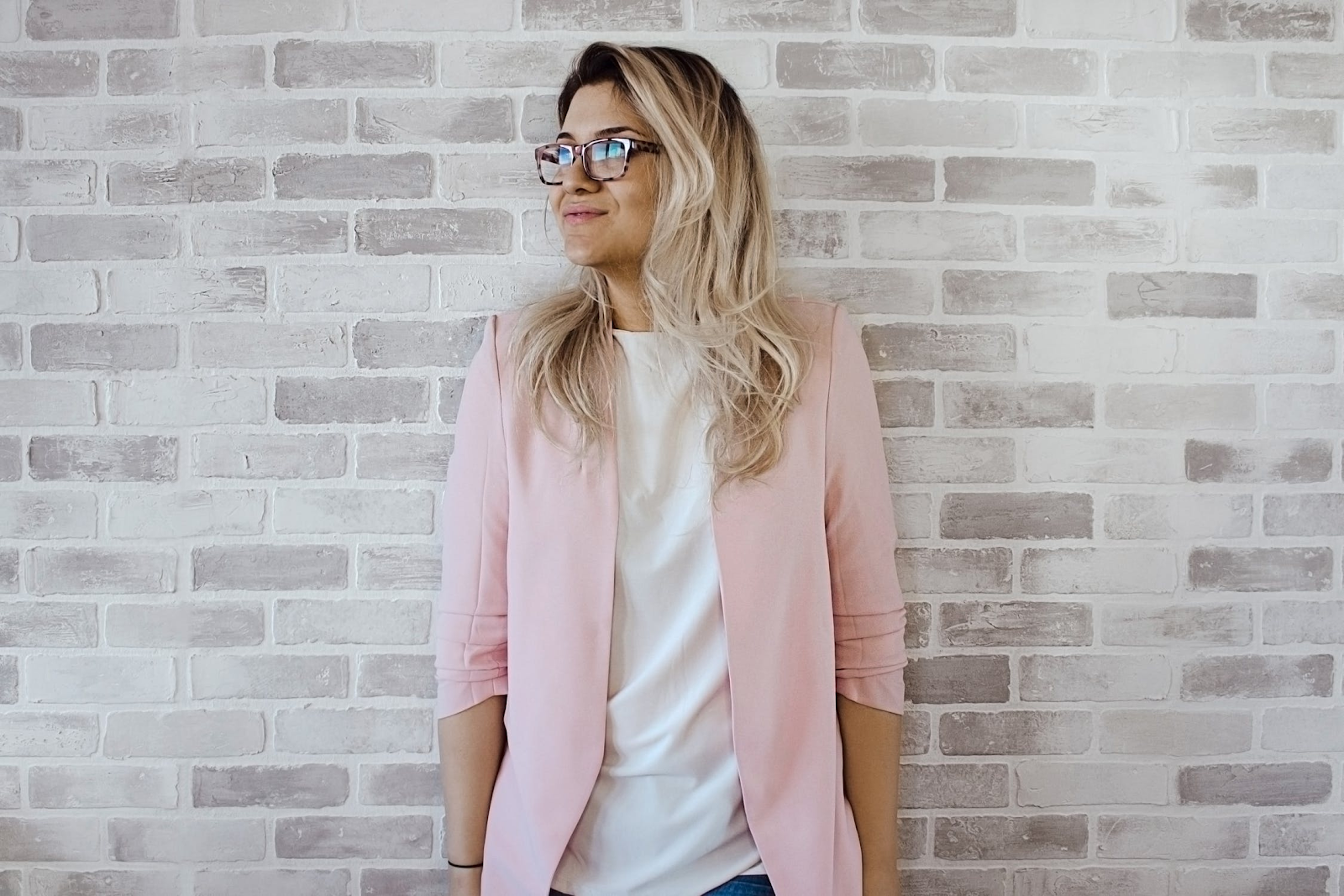 woman with pink jacket leaning on wall