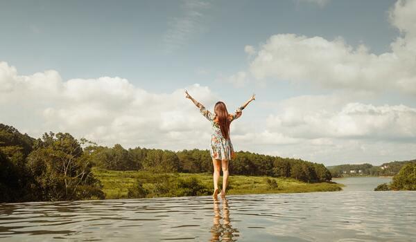 foto de uma mulher com os braços abertos olhando para o céu com os pés na água