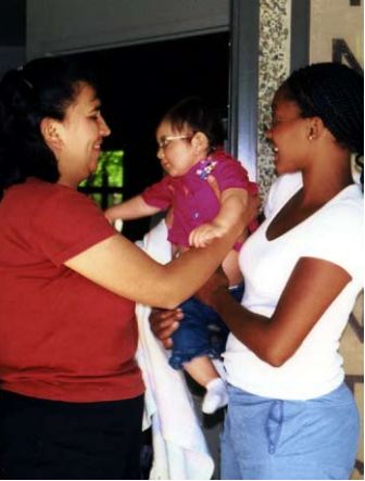 A caregiver handing a chid to a parent