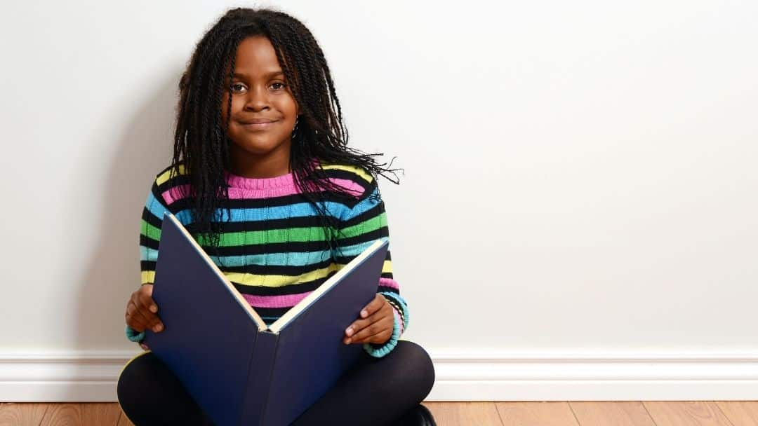 African American 3rd grader smiling at camera with book in her lap