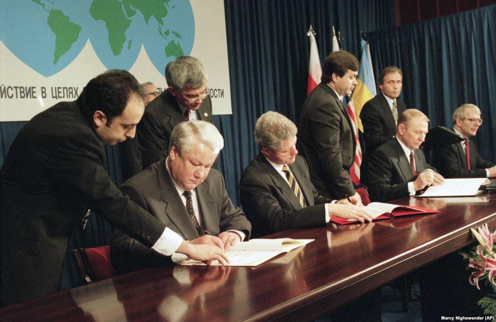 Президент Росії Борис Єльцин (ліворуч), президент США Білл Клінтон (в центрі), президент України Леонід Кучма і прем'єр-міністр Великої Британії Джон Мейджор (праворуч) на церемонії підписання Україною Договору про нерозповсюдження ядерної зброї. Будапешт, 5 грудня 1994 року. Угоду офіційну називають Будапештським меморандумом, й вона вимагає від Росії дотримуватися територіальної цілісності України