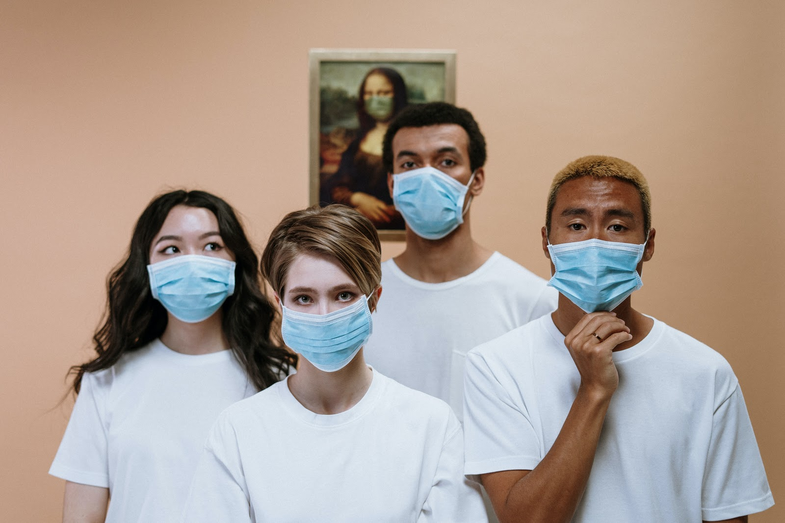 Two men and two women wearing blue face masks and white t-shirts stand in front of a picture of the Mona Lisa wearing a green facemask
