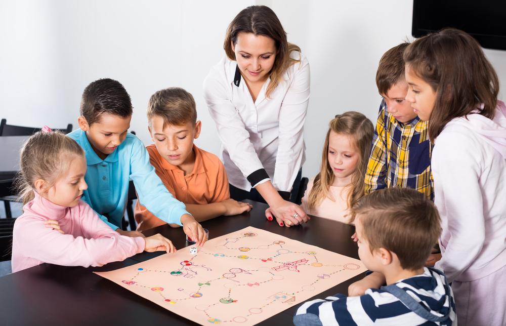 Crianças ao redor do jogo de tabuleiro com orientação de mulher