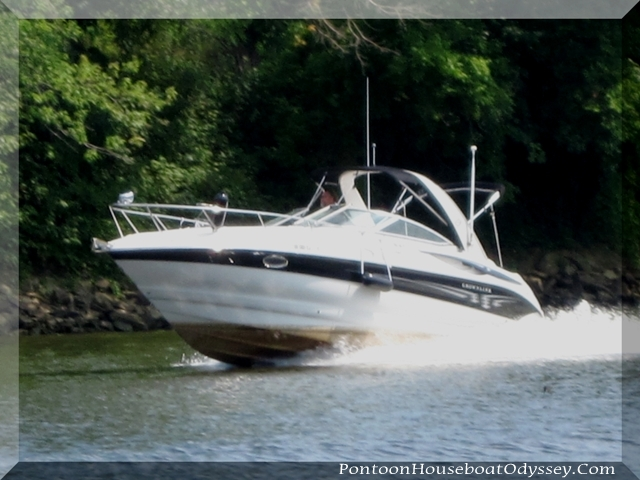 A cabin cruiser up on plane and making wakes on the Muskingum River.