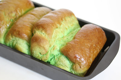 a side-angle photo of pandan bread in a loaf pan