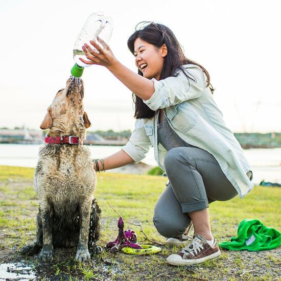 person using Kurgo travel shower to wash muddy dog