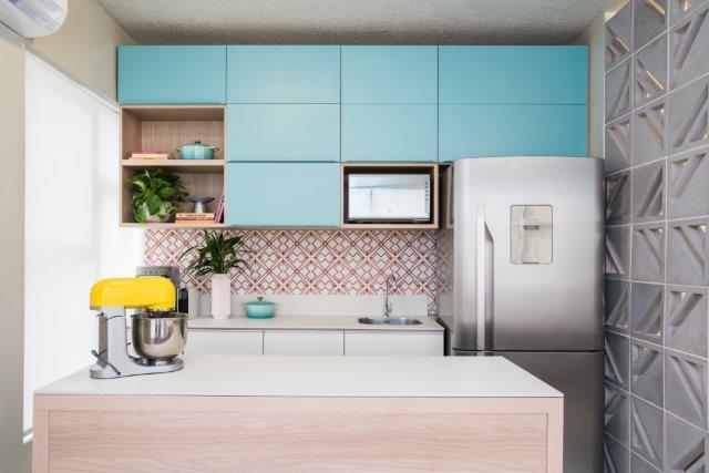 Cozinha em estilo moderno delicado com azulejos geométricos na cor vermelho e branco, bancada de madeira, armário azul claro, geladeira cinza e cobogó cinza.