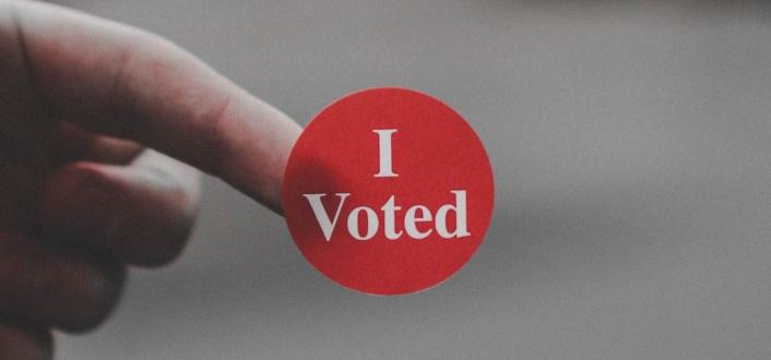 A finger with a red I Voted sticker on the tip