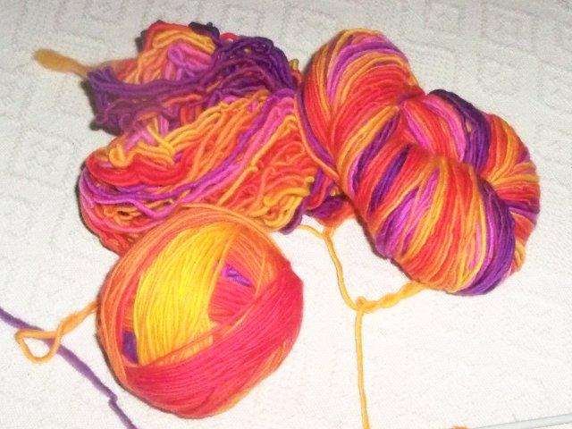 madeja y ovillo de lana naranja, violeta y fuscia