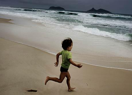 A child running toward a beach.