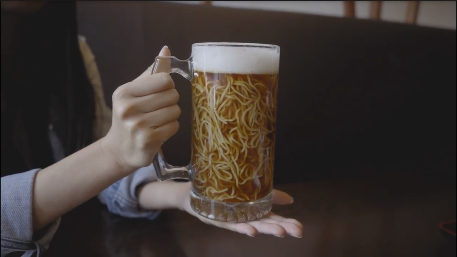 a glass of ramen that looks like beer noodles.