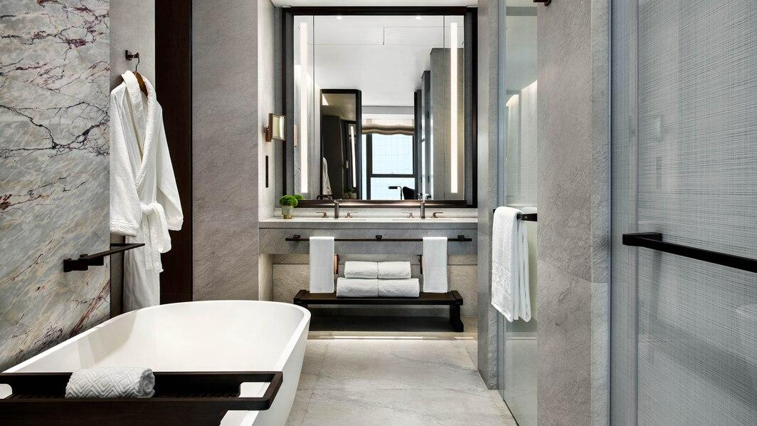 A Bathroom With A Large Mirror  Description Automatically Generated With Low Confidence
