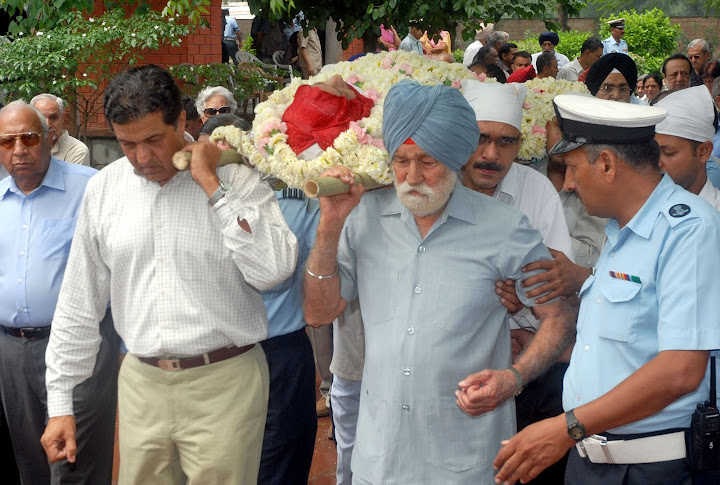 Their last journey together. Marshal of the Indian Air Force Arjan Singh DFC, and his son Arvind Singh carry Teji Arjan Singh at the cremation ground in Delhi on April 17, 2011.