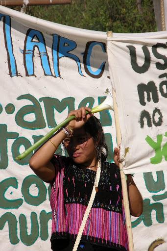 Une femme tient un côté d'une banderole, elle a une fleur dans l'autre main qu'elle tient sur son front pour protéger ses yeux du soleil. Une autre banderole est visible derrière elle. Elle porte un camisole de laine aux couleurs noirs et mauves.